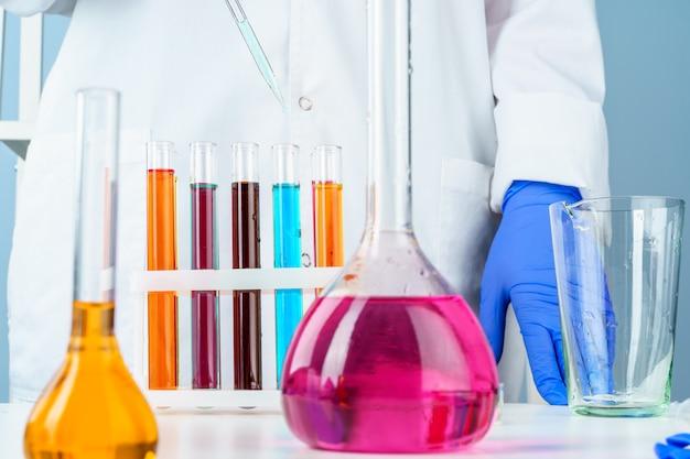 Colored liquids inside lab glassware on white table in laboratory