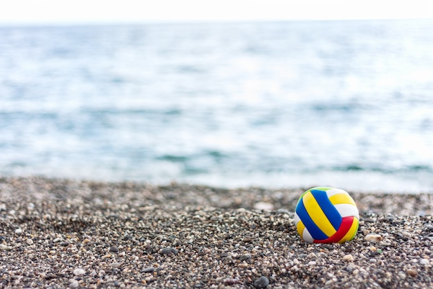 Colored lonely children's ball on a pabble beach on summer sea background.