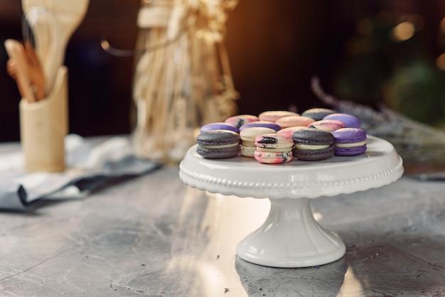 Цветные макаруны на белом подносе на мраморном столе с салфеткой и кухонными принадлежностями