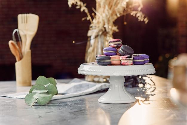 Цветные макароны на белом подносе на мраморном столе с салфеткой, лавандой и кухонными принадлежностями.