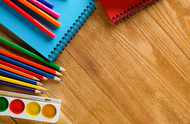 Colored markers and pencils, a clean drawing pad, watercolor paints on a wooden table. subjects of children's creativity, school and preschool education.