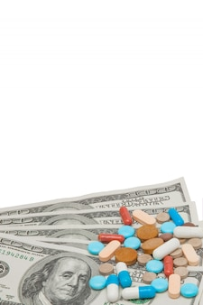 Цветные лекарственные таблетки и американские доллары на белом фоне