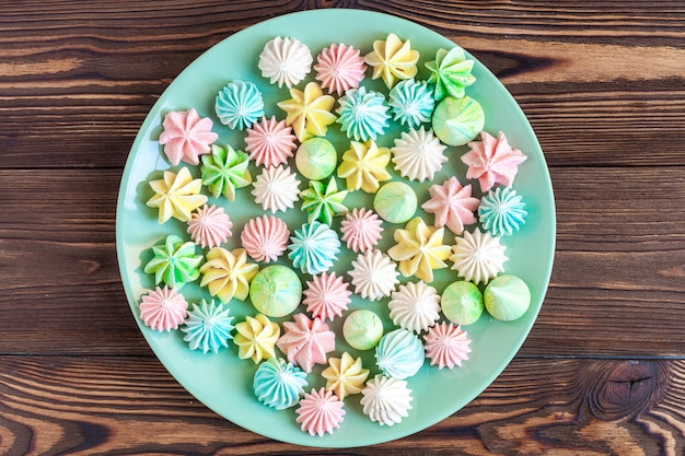 Colored meringues on a plate on wood
