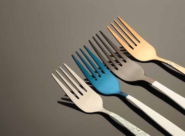 Colored metal forks on a black background