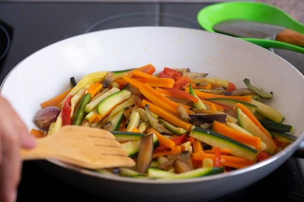 ロールパンに使用するために鍋で炒めたフィレットの新鮮な野菜、ズッキーニ、ニンジン、ピーマン、ナスのカラーミックス