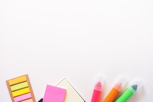 Цветные канцелярские школьные принадлежности из нижней части наклеек маркеров и блокнота на светло-белом