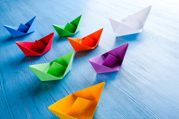 Colored paper boats on a blue table