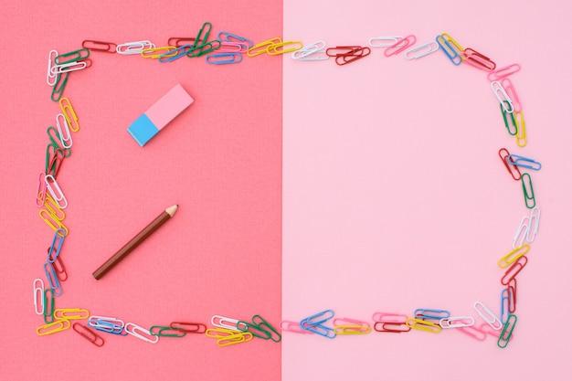 Цветные скрепки в виде рамки и карандаш с ластиком на розово-коралловом фоне. концепция обратно в школу. место для текста.