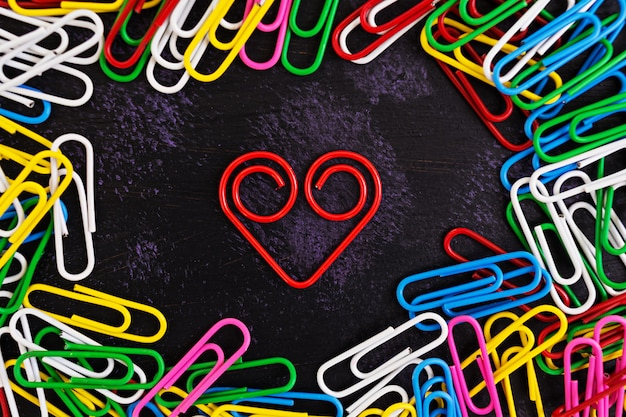 Colored paper clips isolated on dark