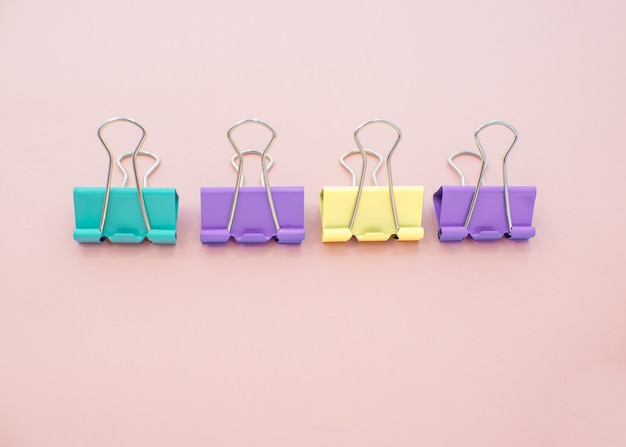Colored paper clips on a pink background. office stationary