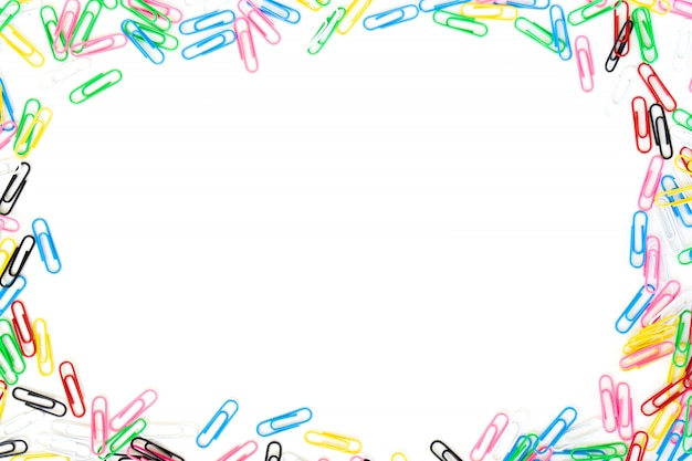 Colored paper clips spread on border with center copyspace isolated on  white