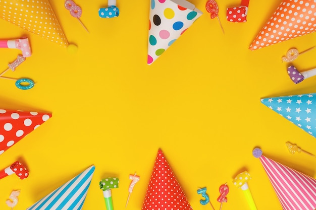 Цветная партийная шляпа и свечи, лежащие на желтом фоне