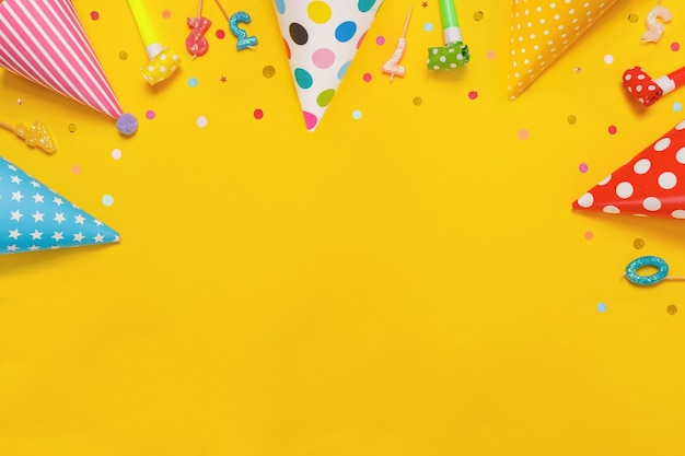 Colored party hat and candles lying on yellow background.