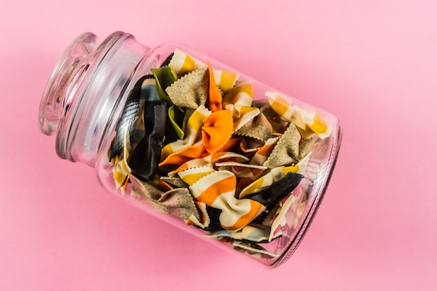 Colored pasta in glass jar on pink background