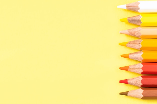 黄色の背景に色鉛筆。テキストの場所。上面図