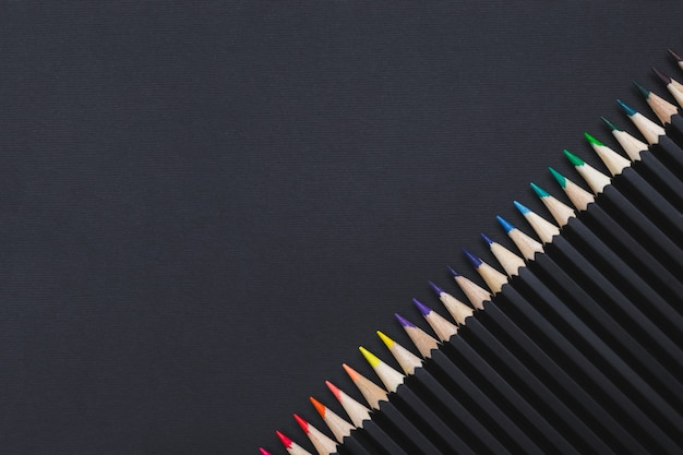 黒の背景に斜めに配置された色鉛筆セット。あなたのデザインのひな形の背景、コピースペース。
