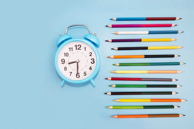 Colored pencils and an alarm clock on a blue background. school concept. back to school.