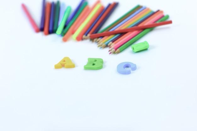 색연필과 흰색 테이블에 알파벳 문자