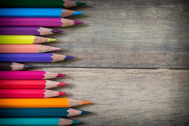 Цветные карандаши и записная книжка на деревянном Бесплатные Фотографии
