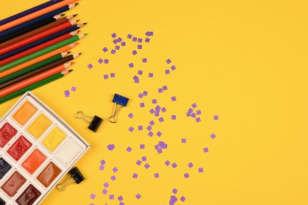 Цветные карандаши и палитра красок на плоской кладке. фото высокого качества