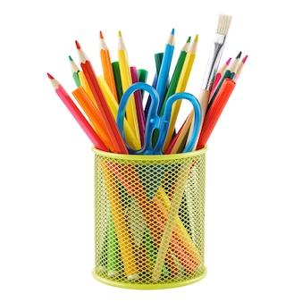 Цветные карандаши и различные канцелярские товары в подставке. изолированные.