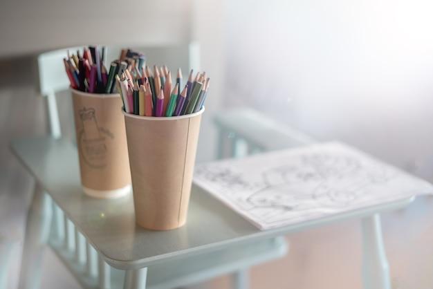 Цветные карандаши на стульчике. теплое и уютное место для рисования и творчества малышей крупным планом.