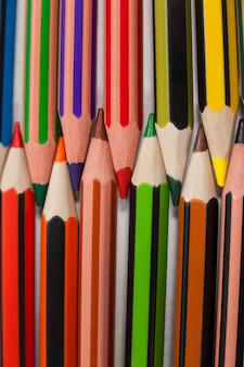 Colored pencils arranged in interlock pattern on white background