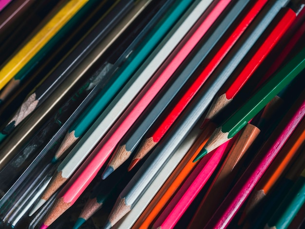 Цветные карандаши фон. закройте различные цвета старых использованных цветных карандашей на стеклянном столе в художественной студии, винтажном стиле тона. инструменты художника для создания произведений искусства.