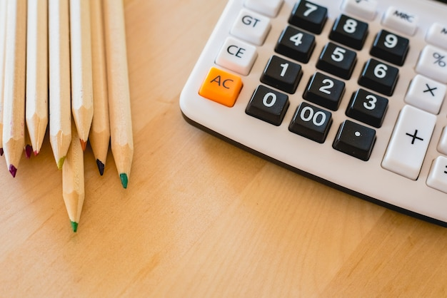 Colored pencils and calculator on a table.