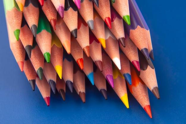 濃い青の背景に描くための色鉛筆。教育と創造性。レジャーとアート