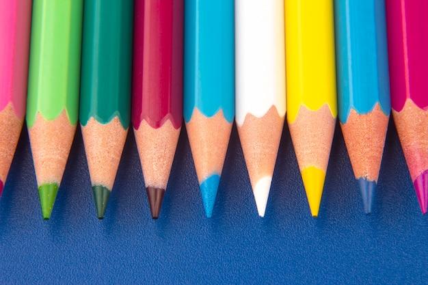 진한 파란색 표면에 그리기위한 색연필. 교육과 창의성. 여가와 예술