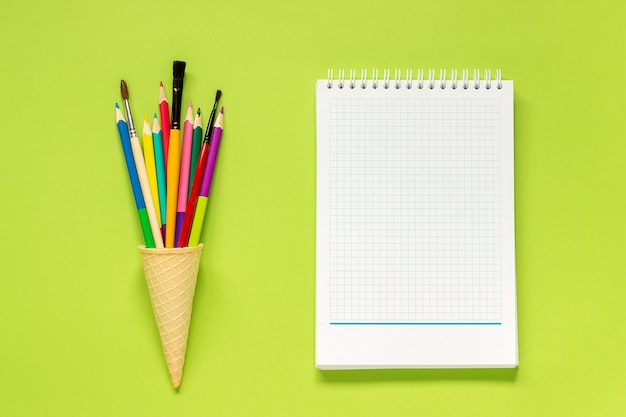 Colored pencils in ice cream cone, notebook on green background. concept back to school