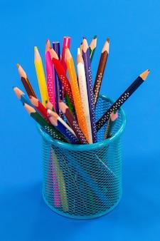 コピースペースと青い背景の上の鉛筆ケースの色鉛筆。