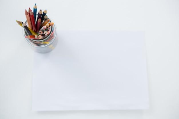 Цветные карандаши в держателе для карандашей на чистом листе бумаги
