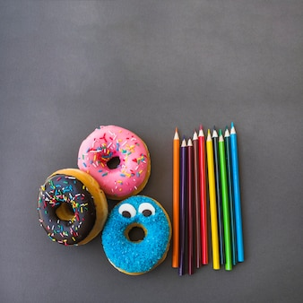 Colored pencils lying near donuts