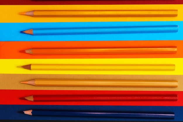 Colored pencils on a multicolored background many pencils of different colors color pencil the penci...