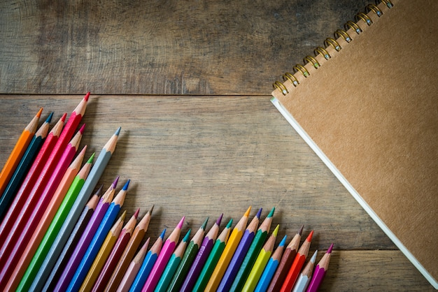 Colored pencils and note book on a wooden