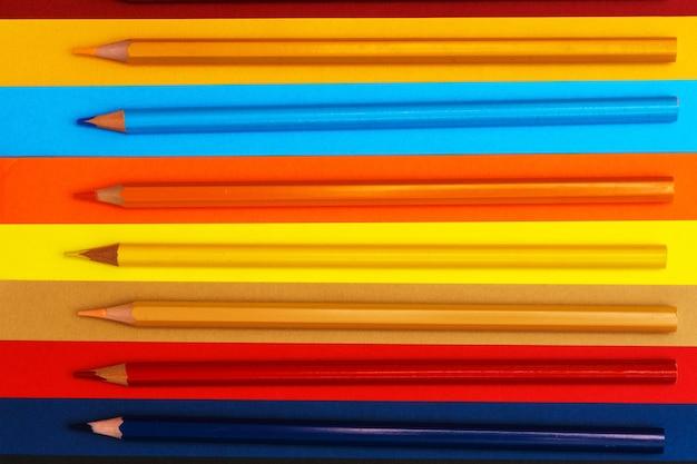 여러 가지 빛깔의 배경에 색연필 다른 색의 많은 연필 색연필 연필...