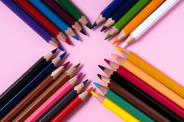 ピンクの背景に色鉛筆。教育の概念。上面図