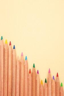 Цветные карандаши на бежевой пастели.