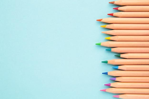 青いパステルカラーの背景に色鉛筆