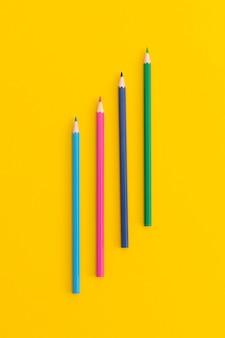 Цветные карандаши на желтом фоне. вид сверху с копией пространства. плоская планировка. снова в школу концепции.