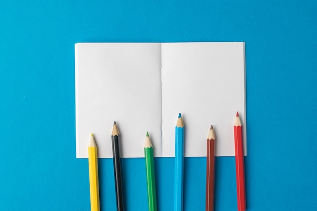 Colored pencils on an open notebook on a blue background. stationery and school supplies.