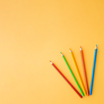 Colored pencils on orange background