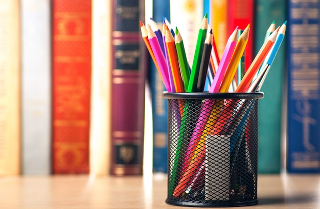 Colored pencils in pencil case on the bookshelf