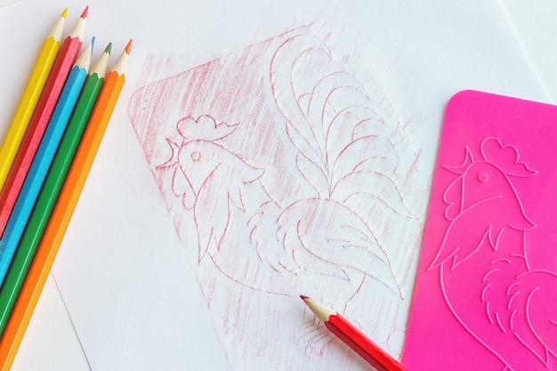 Colored pencils and a relief stencill