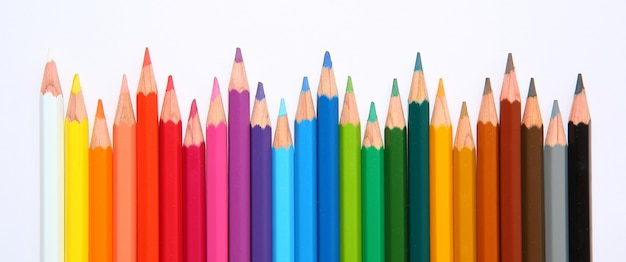 Colored pencils row with wave on white background