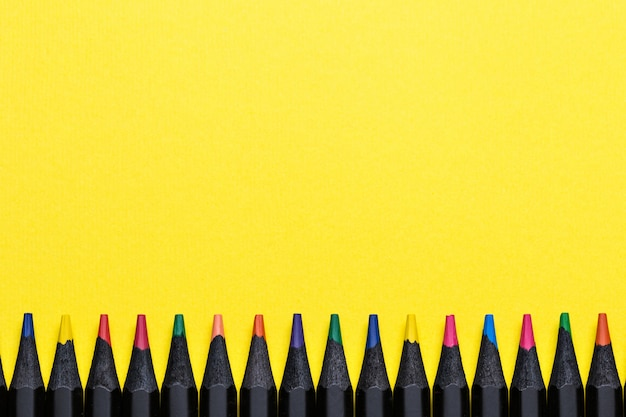 Colored pencils in a row on yellow