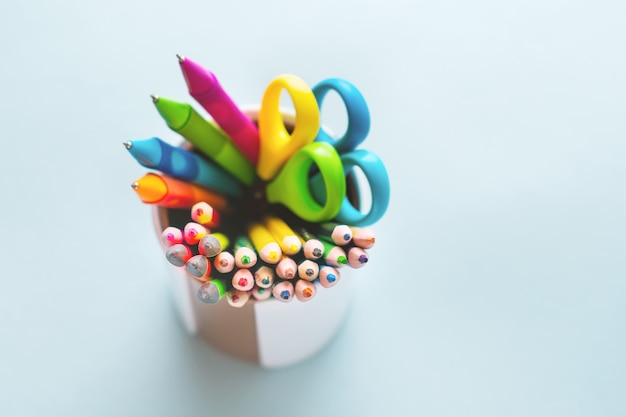 Colored pencils, scissors, notebook, ruler, pen, eraser, sharpener and more in glass, school and office stationery on light blue background.
