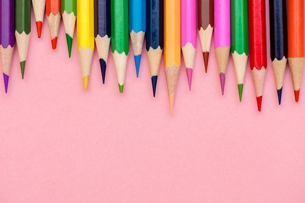 ピンクの背景に設定された色鉛筆
